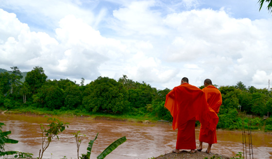 Scenic photo of Buddhist monks by a lake in Laos